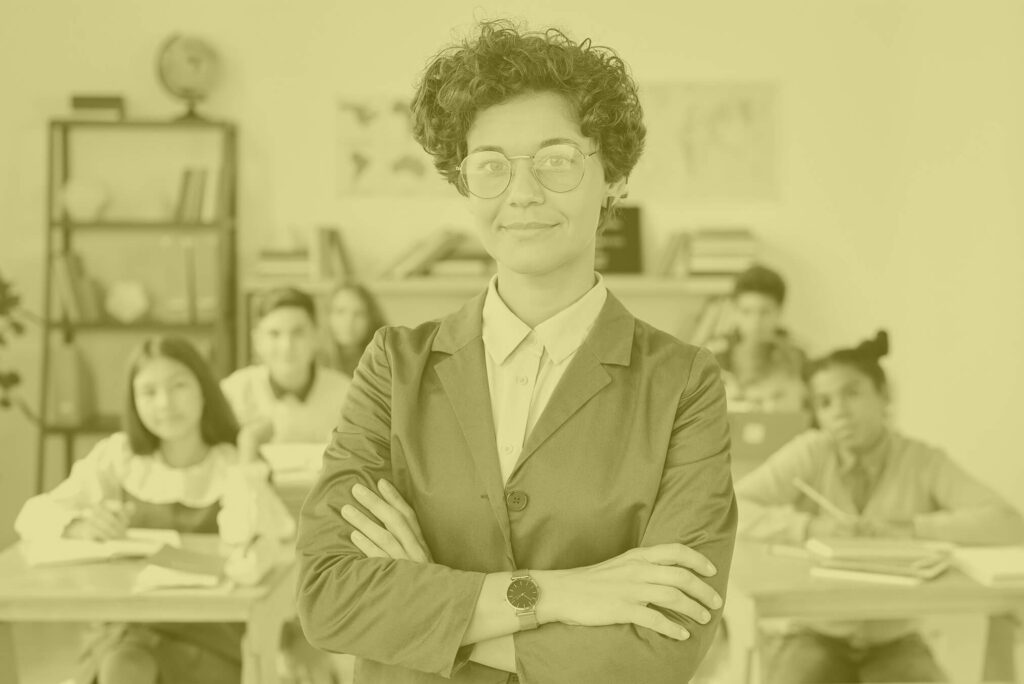 A female teacher stands arms crossed but smiling in front of children sitting in a classroom.